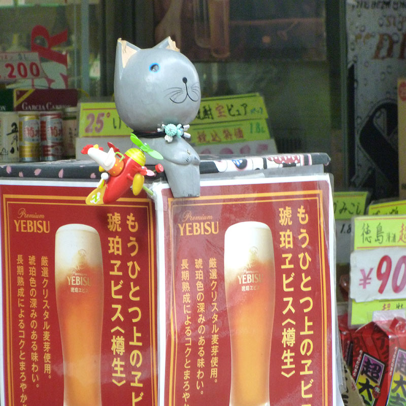Cat ornaments sitting on a beer sign in Yanaka Ginza
