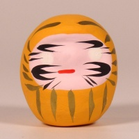 Mini traditional Japanese Daruma doll in yellow