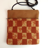 Pochette style handbag in brick orange with a check design