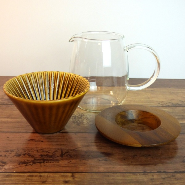 Clear glass coffee jug, caramel-coloured ceramic filter cone and wooden holder