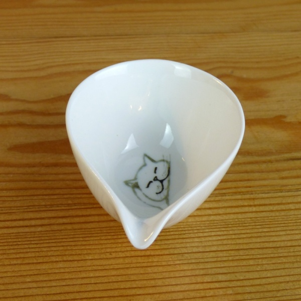 Small white milk jug inside cat decoration