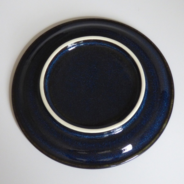 Underside of dark blue ceramic saucer