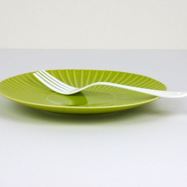 White enamel dessert fork on green plate