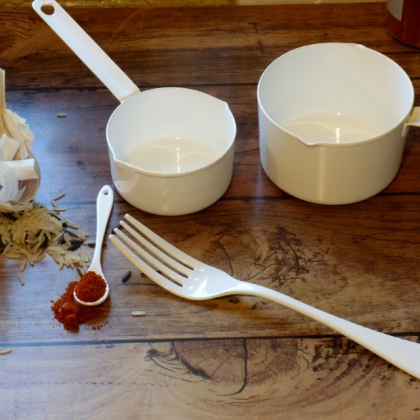 White enamel mustard spoon with other kitchen implements