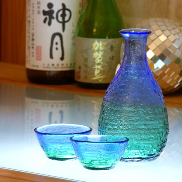 'Ocean' blue green glass sake jug and cups on bar