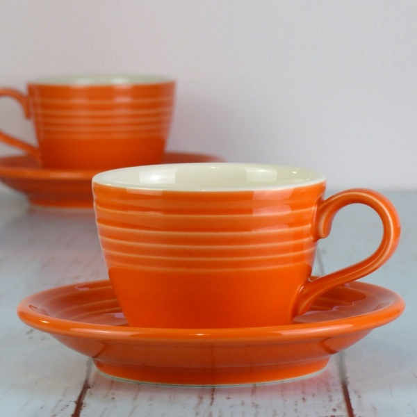 Mandarin orange coffee cup and saucer on pale work surface