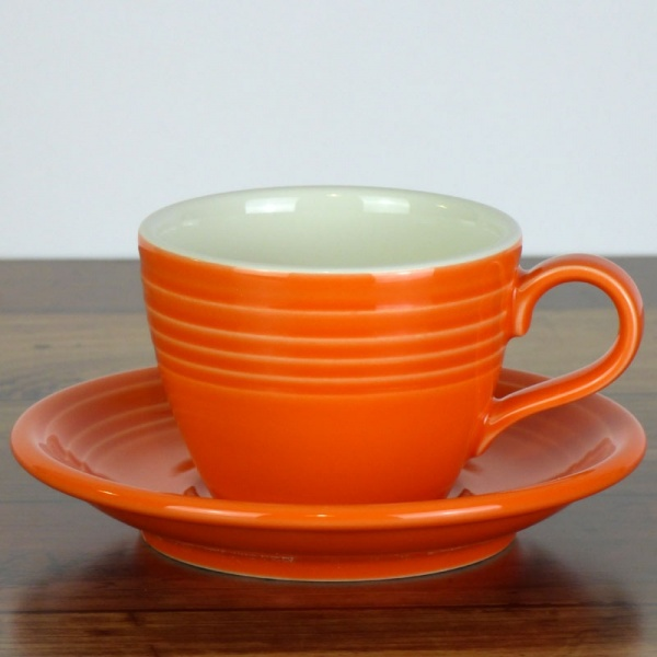 Mandarin orange coffee cup and saucer on wood work surface