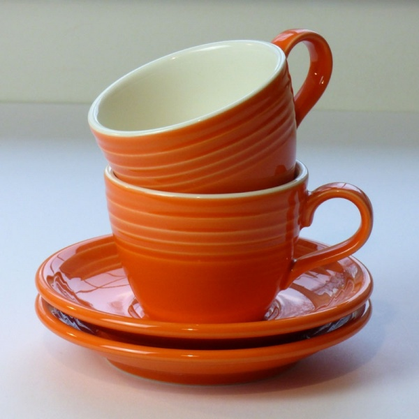 Stack of Mandarin orange coffee cups and saucers
