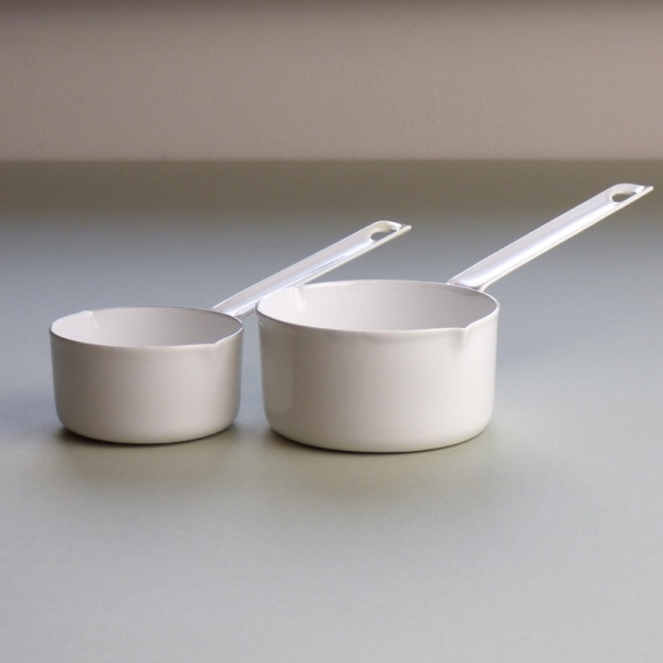 Two white enamel measuring cups