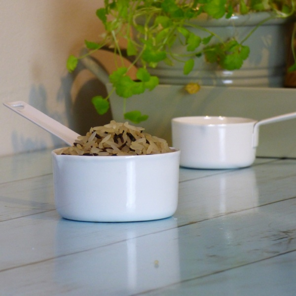 Two white enamel measuring cups in kitchen