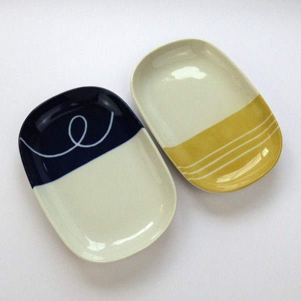 Oval plates, one with navy blue dipped glaze and the other with yellow dipped glaze design