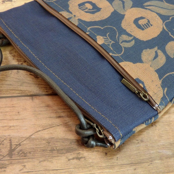 Close up of indigo blue pochette style handbag with Camellia flower design