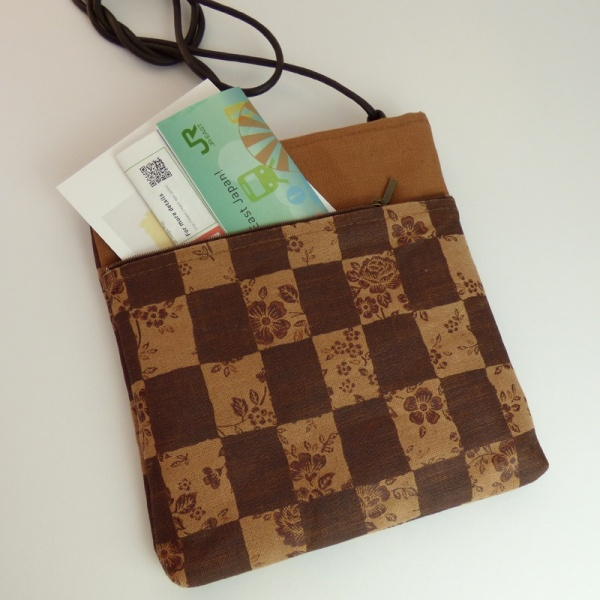 Pochette style handbag in tan and dark brown with a check design