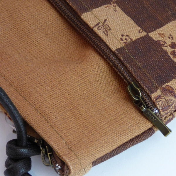 Close up of Pochette style handbag in tan and dark brown with a check design