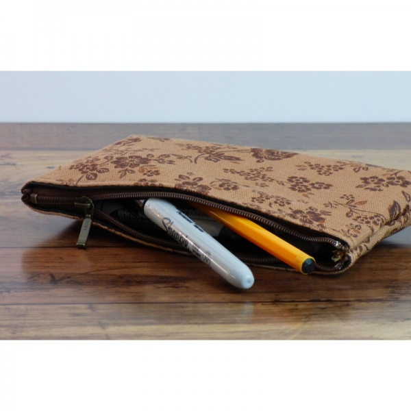 Canvas zip bag with brown floral design in use as a pencil case