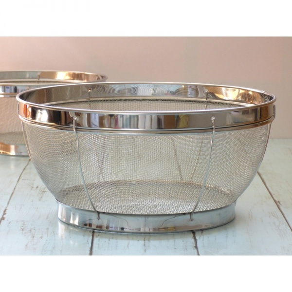 Large stainless steel sieve on kitchen work surface
