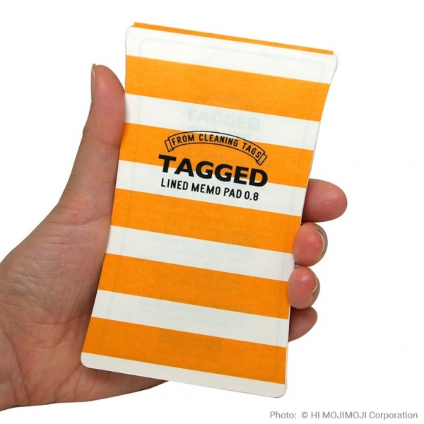 'Tagged' Japanese notepad with Yellow Stripe cover held in hand