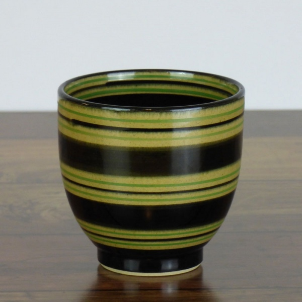 Black Japanese tea cup with green stripe pattern on dark kitchen surface