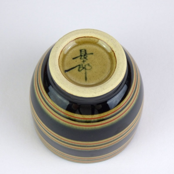 Black Japanese tea cup with red stripe pattern underside