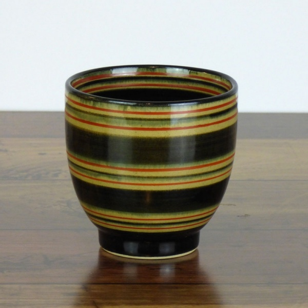 Black Japanese tea cup with red stripe pattern on dark kitchen surface