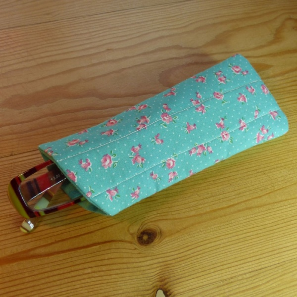 Handmade quilted glasses case in turquoise rose print - shown with glasses