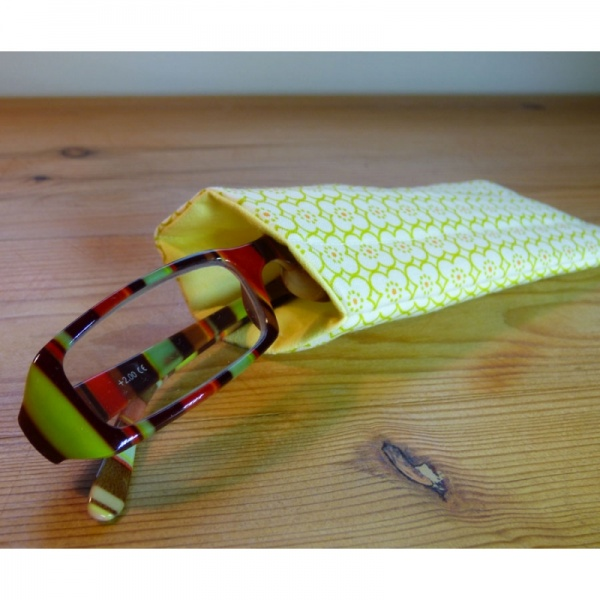 Handmade quilted glasses case in a yellow geometric print - shown with glasses