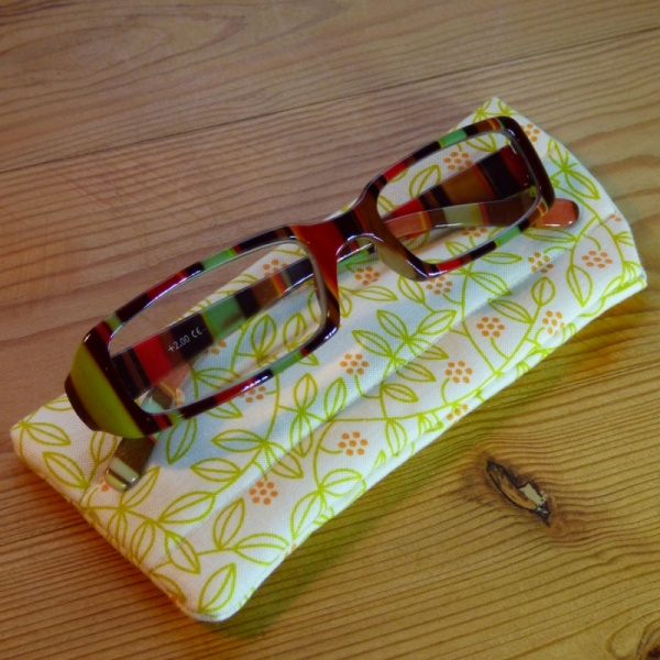 Handmade quilted glasses case in yellow leaf print - shown with glasses